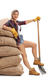 Female farmer leaning on pile of burlap sacks and holding a shov Royalty Free Stock Photos