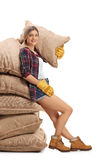 Female farmer leaning on a pile of burlap sacks royalty free stock photo