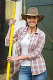 Female farmer pitch fork. Happy female farmer holding a pitch fork inside stable Royalty Free Stock Photography