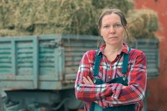 Female farmer posing in front of hay wagon. Portrait of woman farm worker in plaid shirt and bib overalls by the tractor trailer filled with dairy farm royalty free stock images