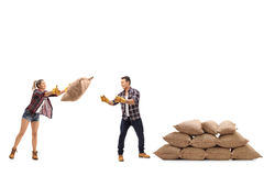 Female farmer throwing a burlap sack at a male farmer royalty free stock photography