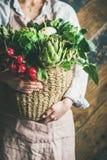 Female farmer in apron holding basket with fresh vegetables. Female farmer wearing pastel linen apron and shirt holding basket with fresh seasonal vegetables in Stock Image