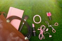 Fashion accessories - bag, note pad, headphones, lipstick and other essentials on the grass. Female fashion accessories - bag, note pad, headphones, lipstick and Stock Photos