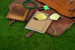 Fashion accessories - bag, note pad, purse, nail polish essentials on the grass. Female fashion accessories - bag, note pad, purse, nail polish essentials on the Royalty Free Stock Images