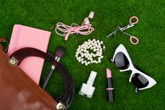 Fashion accessories - bag, note pad, sunglasses, headphones, lipstick and other essentials on the grass. Female fashion accessories - bag, note pad, sunglasses Royalty Free Stock Image