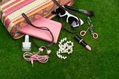 Fashion accessories - bag, note pad, sunglasses, headphones, lipstick and other essentials on the grass. Female fashion accessories - bag, note pad, sunglasses Royalty Free Stock Photo