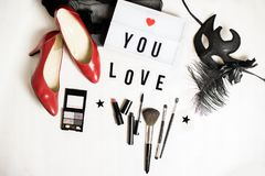Female fashion accessories flat. Top view to female accessories: red shoes with high heels, make up set, a mask, a note I love you Stock Image