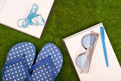 Fashion accessories - flip flops, book, note pad, pen, headphones, note pad, sunglasses on the grass. Female fashion accessories - flip flops, book, note pad Royalty Free Stock Photos