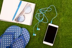 Fashion accessories - flip flops, smart phone with headphones, note pad, sunglasses on the grass. Female fashion accessories - flip flops, smart phone with Stock Images