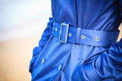 Female fashion. Closeup blue coat wit belt Royalty Free Stock Image