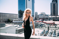 Female fashion concept. Outdoor waist up portrait of young beautiful woman posing on old street. Model wearing stylish clothes, lo Stock Photography