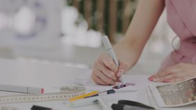 Female fashion designer with beautiful manicure drawing sketches. Measure tape or sentimentr, pencil, markers on the stock footage