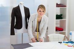 Female fashion designer cutting fabric Stock Image