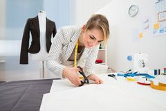 Female fashion designer cutting fabric Royalty Free Stock Photo