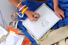 Female fashion designer hands holding drawing pad and pen making. Sketch of new dress. Style and design development and creating garment, clothes sew and repair stock photography