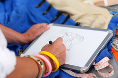Female fashion designer hands holding drawing pad and pen making Royalty Free Stock Photography