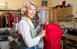 Female fashion designer hemming new clothes on mannequin Royalty Free Stock Photography