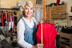 Female fashion designer hemming new clothes on mannequin Stock Photography