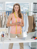 Female fashion designer with laptop and cellphone in studio Stock Photography