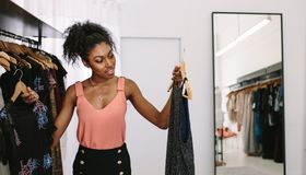 Woman entrepreneur in her fashion boutique. Female fashion designer looking at designer dresses in her fashion studio. Customer comparing dresses in a fashion Royalty Free Stock Photo