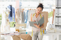 Female fashion designer looking at folder Stock Images
