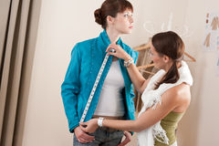 Female fashion designer measuring jacket on model Stock Image