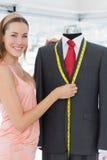 Female fashion designer measuring suit on dummy Royalty Free Stock Photo