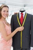 Female fashion designer measuring suit on dummy Stock Photo