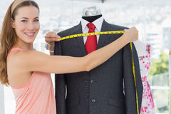 Female fashion designer measuring suit on dummy Royalty Free Stock Photography