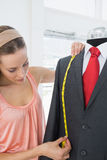 Female fashion designer measuring suit on dummy Stock Photos