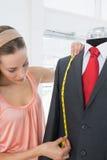 Female fashion designer measuring suit on dummy Stock Photos