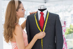 Female fashion designer measuring suit on dummy Royalty Free Stock Image