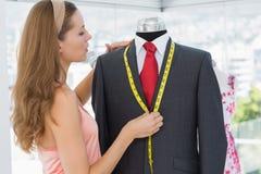 Female fashion designer measuring suit on dummy Royalty Free Stock Image