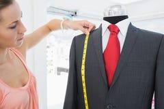 Female fashion designer measuring suit on dummy Royalty Free Stock Photography