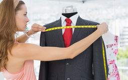 Female fashion designer measuring suit on dummy Royalty Free Stock Images