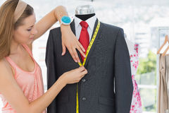 Female fashion designer measuring suit on dummy Stock Image