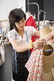 Female fashion designer pinning costume on mannequin Royalty Free Stock Images