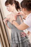 Female fashion designer pinning dress on model Stock Photography