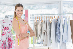 Female fashion designer with rack of clothes in store Stock Photo
