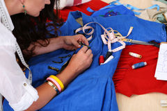Female fashion designer sewing accessories to blue retro style d Royalty Free Stock Photo