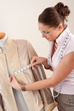 Female fashion designer taking measurement Stock Photo
