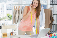 Female fashion designer using laptop and cellphone in studio Stock Images
