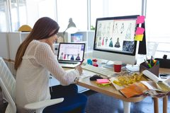 Female fashion designer working at desk in a modern office. Side view of young Caucasian female fashion designer working at desk in a modern office royalty free stock photography