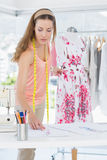 Female fashion designer working on floral dress. Beautiful female fashion designer working on floral dress at the studio Royalty Free Stock Photo