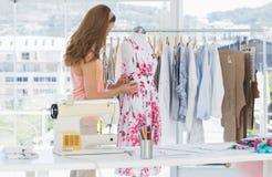 Female fashion designer working on floral dress. Side view of a beautiful female fashion designer working on floral dress at the studio Stock Photo