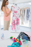Female fashion designer working on floral dress at studio Royalty Free Stock Photography