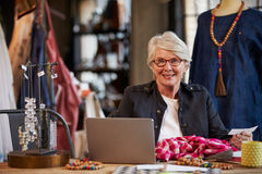 Female Fashion Designer Working At Laptop In Studio Royalty Free Stock Images