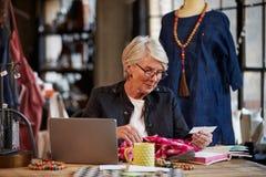 Female Fashion Designer Working At Laptop In Studio Stock Photo
