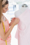Female fashion designer working on pink fabric Stock Image