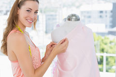 Female fashion designer working on pink fabric Stock Photos